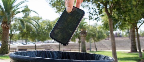 A hand dropping a smartphone into a trash can.