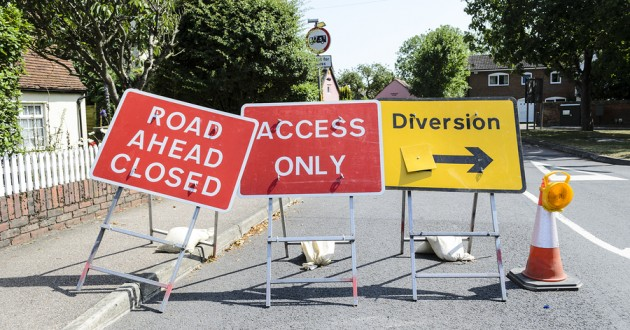 A trio of road signs blocking access.