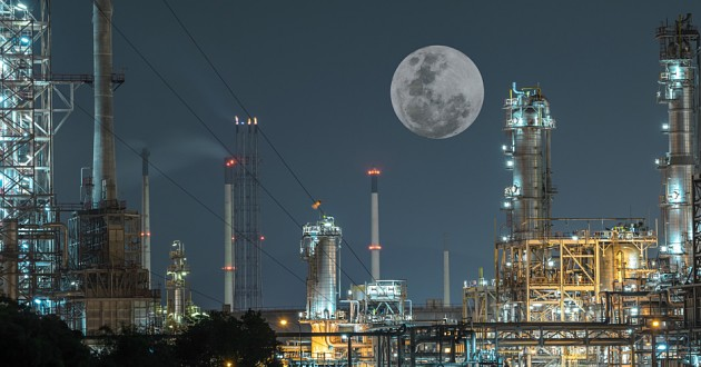 Oil and gas refinery plant under a large full moon.