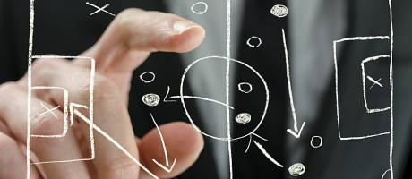A businessman pointing to an illustration of an offensive strategy.