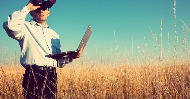 A businessman in a field looking through binoculars and holding a laptop.
