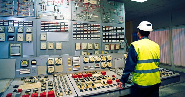 A worker in an industrial control room.