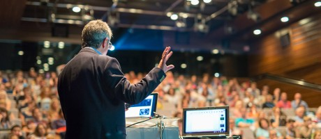 A business professional delivering a speech to an audience at an industry conference.