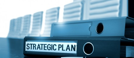 """A binder labeled """"strategic plan"""" sitting on a boardroom table."""