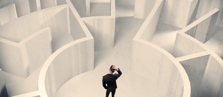 A businessman standing in the center of a circular maze.