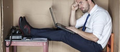 A businessman working inside a cramped, cardboard box.