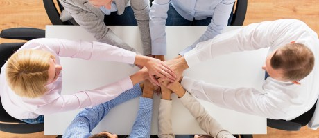 A group of business professionals joining hands around a table.