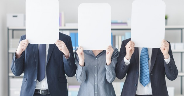 Three businesspeople covering their faces with white boards.