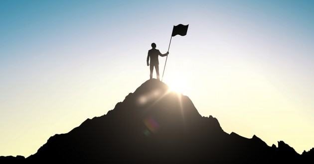 A silhouette of a climber planting a flag at the peak of a mountain.