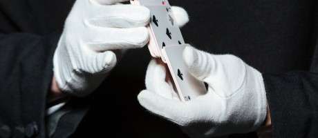 Closeup of a magician's hands in white gloves shuffling playing cards.
