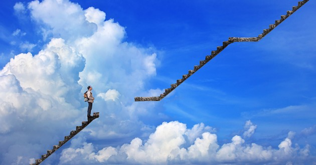 A man standing before a gap in a staircase to the clouds.