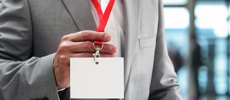 A businessman displaying an ID badge to gain access to a privileged area.