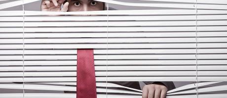A businessman hiding and peeking through window blinds.