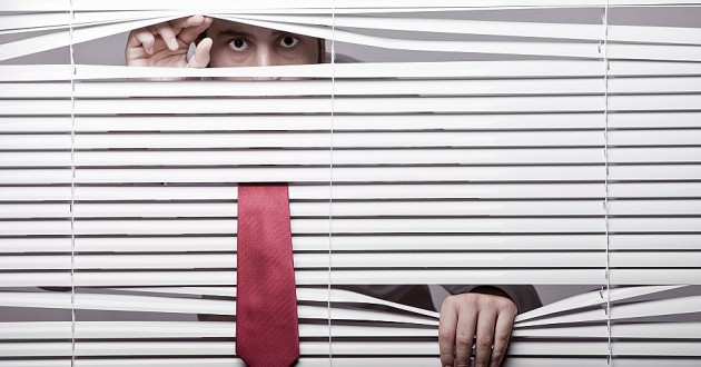 A businessman hiding and peeking through window blinds.