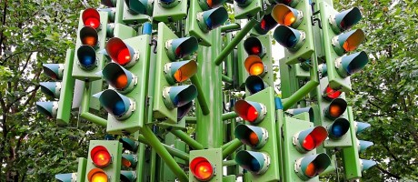 A cluster of traffic lights in a forest.