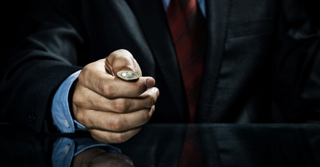 A businessman preparing to flip a coin.