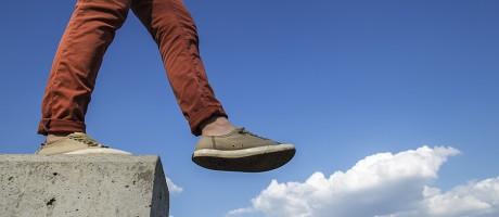 A man walking off a cement ledge.