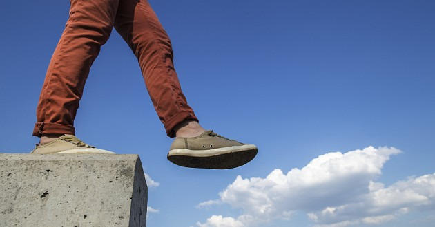 A man walking off a cement ledge.