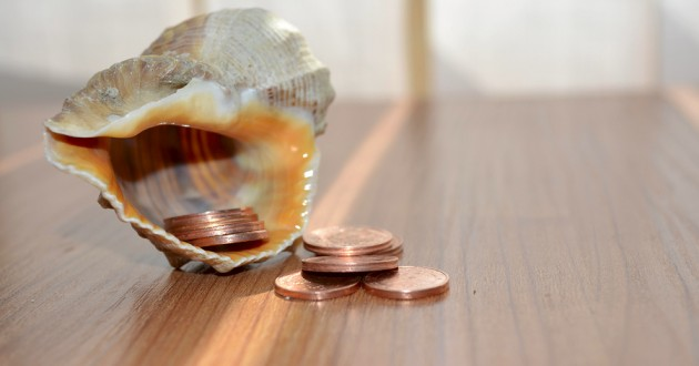 Pennies falling out of a seashell on a wooden desk.