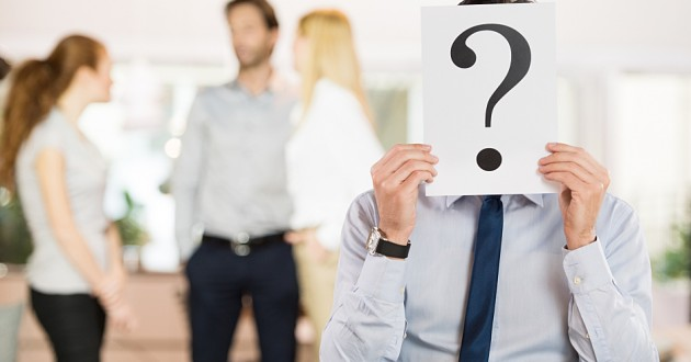 An employee holding a card with a question mark over his face.