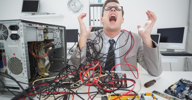 An IT engineer tangled in computer cables.