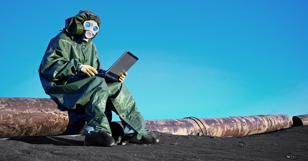 An environmental scientist working on a laptop in a chemically contaminated area.