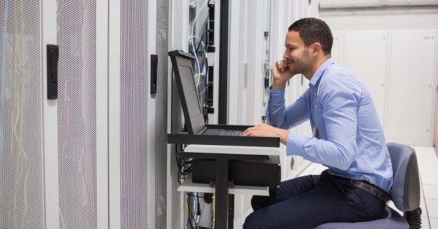 A security analyst working on a computer in front of network servers.