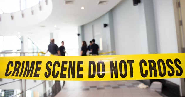 Crime scene tape in front of police officers.