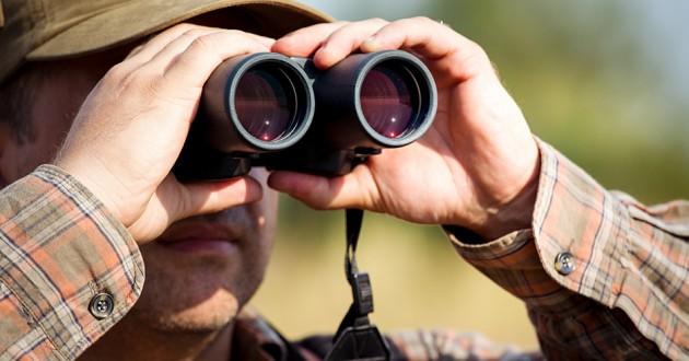 A hunter looking through binoculars.