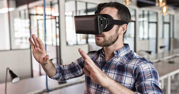A man using a virtual reality device in an office.