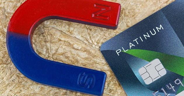 A magnet beside a credit card on a wooden surface.