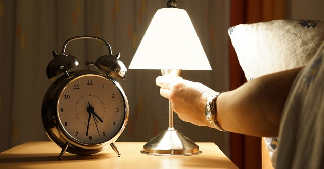 A man in bed turning on a light next to an alarm clock on a nightstand.
