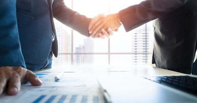 Two businessmen shaking hands over an office desktop.