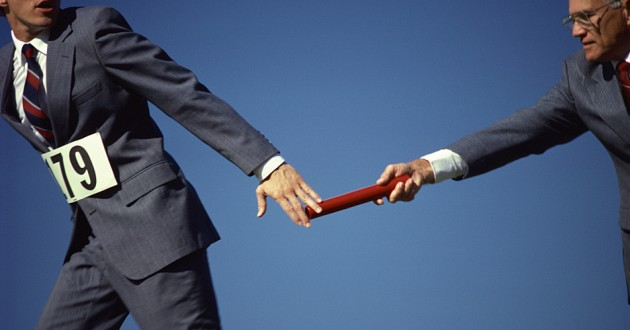 Men in business suits exchanging a baton in a relay race.