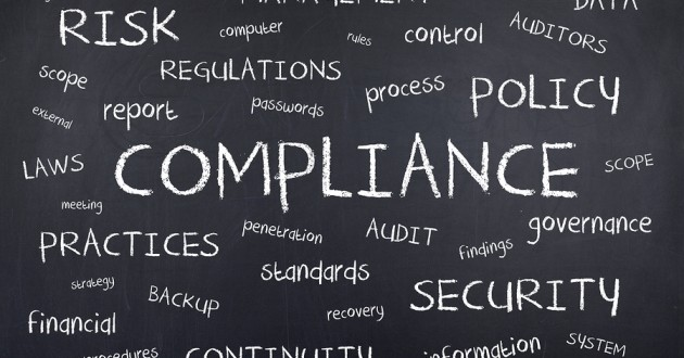 """Buzzwords like """"Compliance"""" and """"Security"""" written on a chalkboard."""