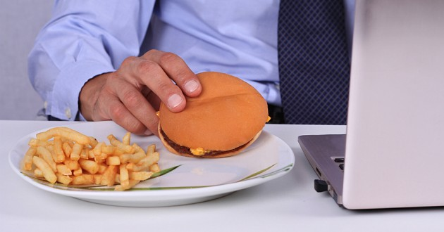 A man eating a cheeseburger and fries while using a laptop computer.