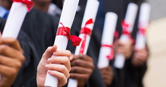 Multiple graduates holding diplomas and certificates.