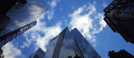 Skyscrapers beneath a blue sky dotted with clouds.