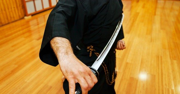 An instructor in a dojo with a katana