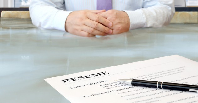 A job resume in front of a businessman sitting at a table.