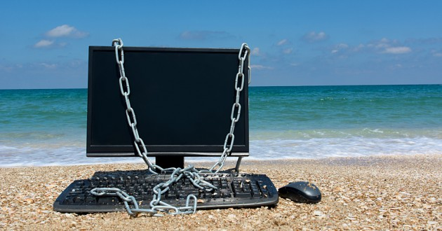 A computer monitor and keyboard draped in chains on a beach.