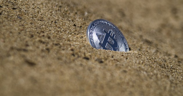 A coin bearing the bitcoin logo partially buried in sand.