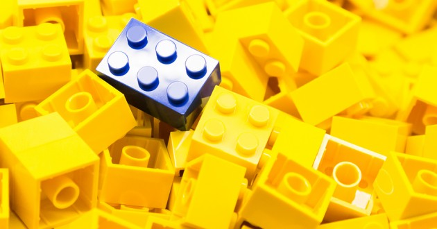 A pile of yellow building blocks with one blue block on top.