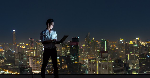 A businessman using a laptop in front of a window overlooking a city.