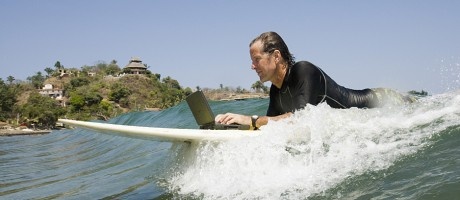A man typing on a laptop while lying on a surfboard.