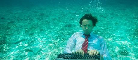 A man typing on a computer keyboard underwater.