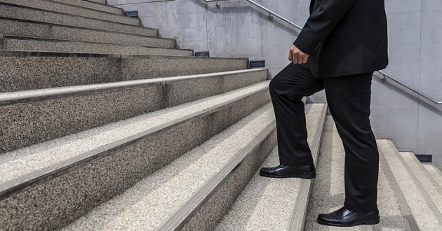 A businessman walking up stairs.