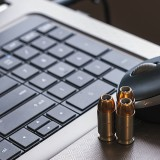 Three bullet casings on a computer keyboard.