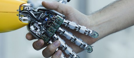 Robot hand and a human hand forming a handshake.