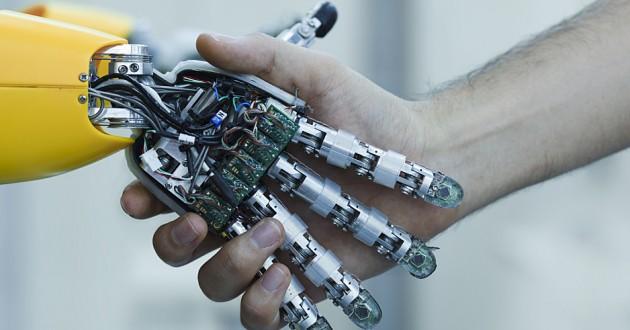 Robot hand and a human hand forming a handshake.